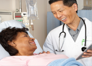 International doctor discussing with patient at bedside